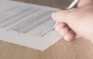 Hand, die einen schriftlichen Widerspruch bei der TK unterschreibt